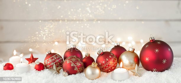 1020742072istockphoto Christmas holiday baubles festive and sparkling lights against a wood background 1026760900
