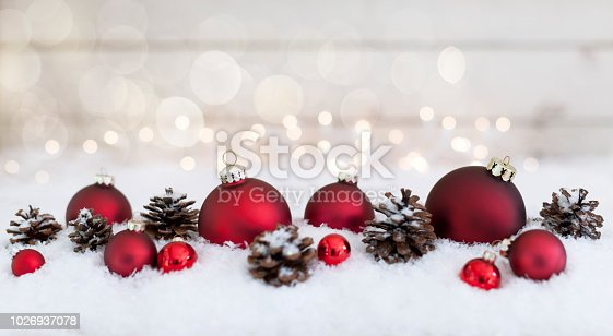 1020742072istockphoto Christmas holiday baubles festive and sparkling lights against a wood background 1026937078