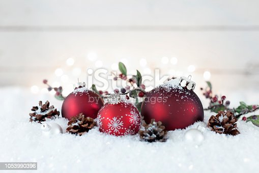 Christmas holiday baubles in snow against defocused Christmas lights on an old wood background