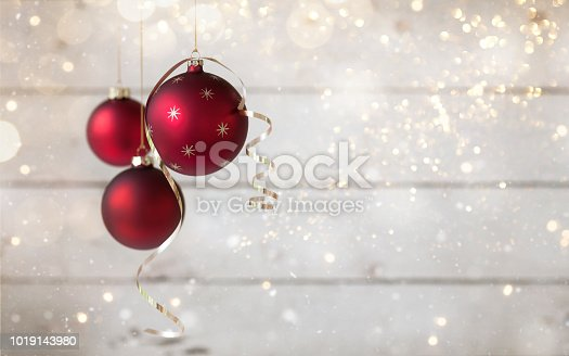 Christmas holiday baubles with signature ribbon, festive and sparkling lights against an old wood background
