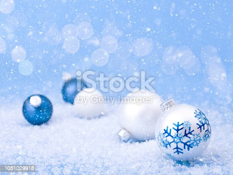 Christmas holiday blue and white snowflake themed baubles on a reflective surface with snow and defocused lights