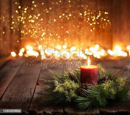 Christmas holiday glowing candle and wreath on a wood background