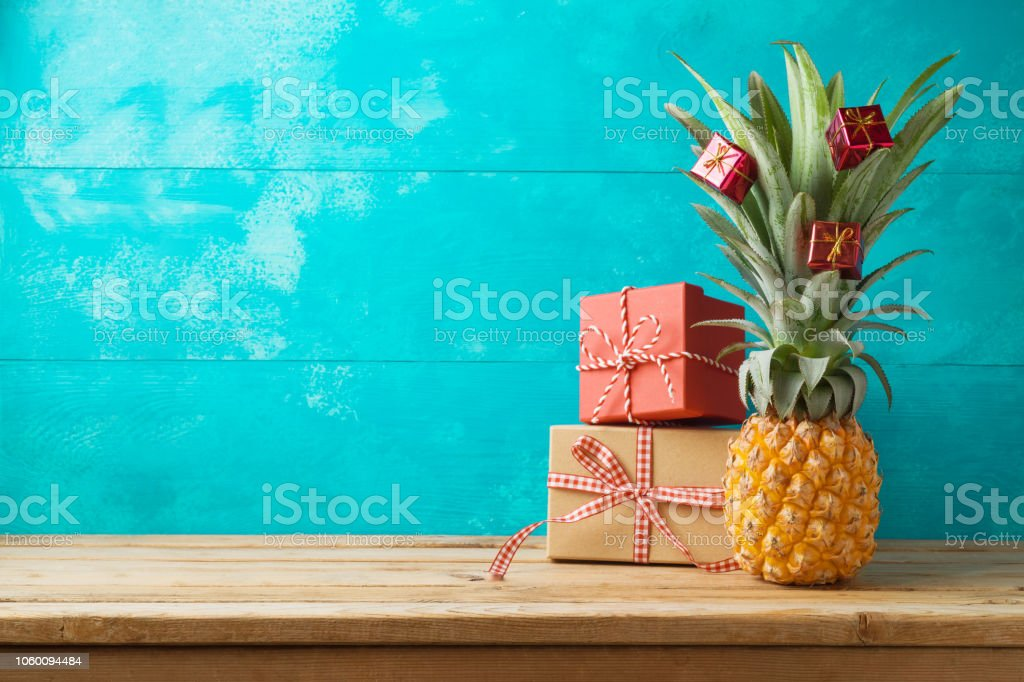 Christmas holiday concept with  pineapple as alternative Christmas tree and gift boxes on wooden table with copy space stock photo