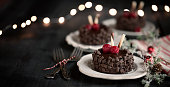 Tasty chocolate cake with berries and green leafs on dark background. Concept of birthday holiday food. Free space for text