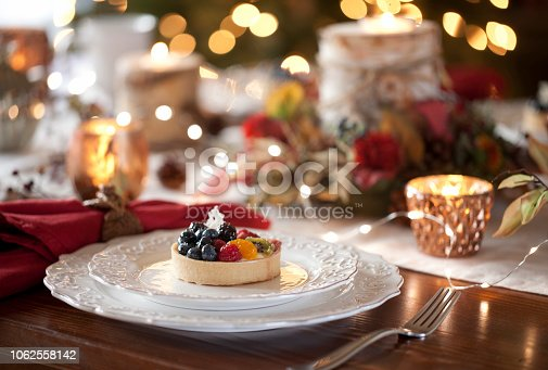 Christmas or holiday dining with dessert fruit tart.