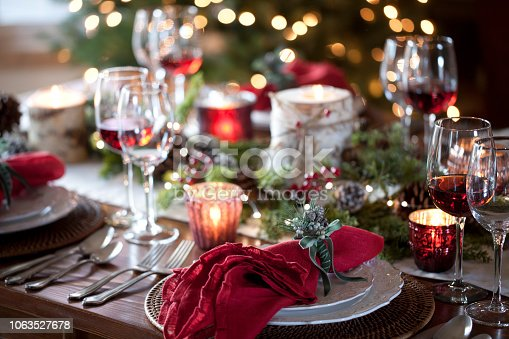 Christmas holiday dining table elegant place setting. Very shallow depth and dramatic lighting
