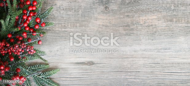 Christmas Holiday Evergreen Pine Branches and Red Berries Over Wood Background, Copy Space