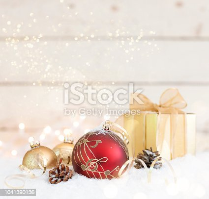 1020742072istockphoto Christmas Holiday Music Themed Bauble and a Gift on an Old Wooden Background 1041390136