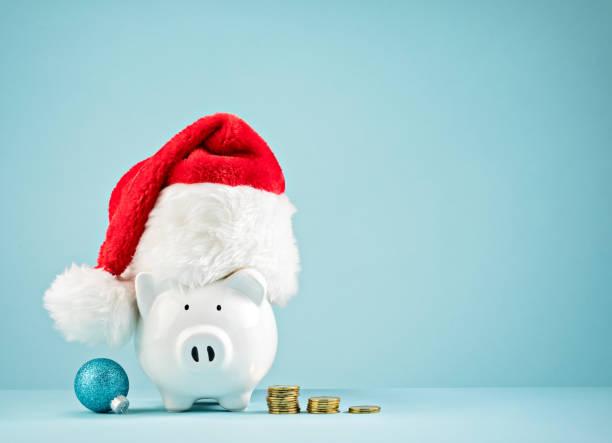 Christmas Holiday piggy bank wearing santa hat stock photo