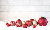 Christmas holiday red and gold baubles, festive and sparkling lights against an old wood background