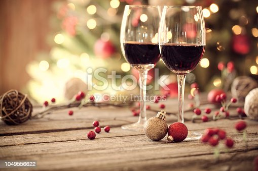 Christmas holiday red wine on a rustic wooden table in front of a Christmas tree. Very shallow depth