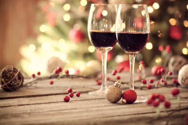 weihnachten urlaub roten wein vor einem weihnachtsbaum - roten küchentische stock-fotos und bilder