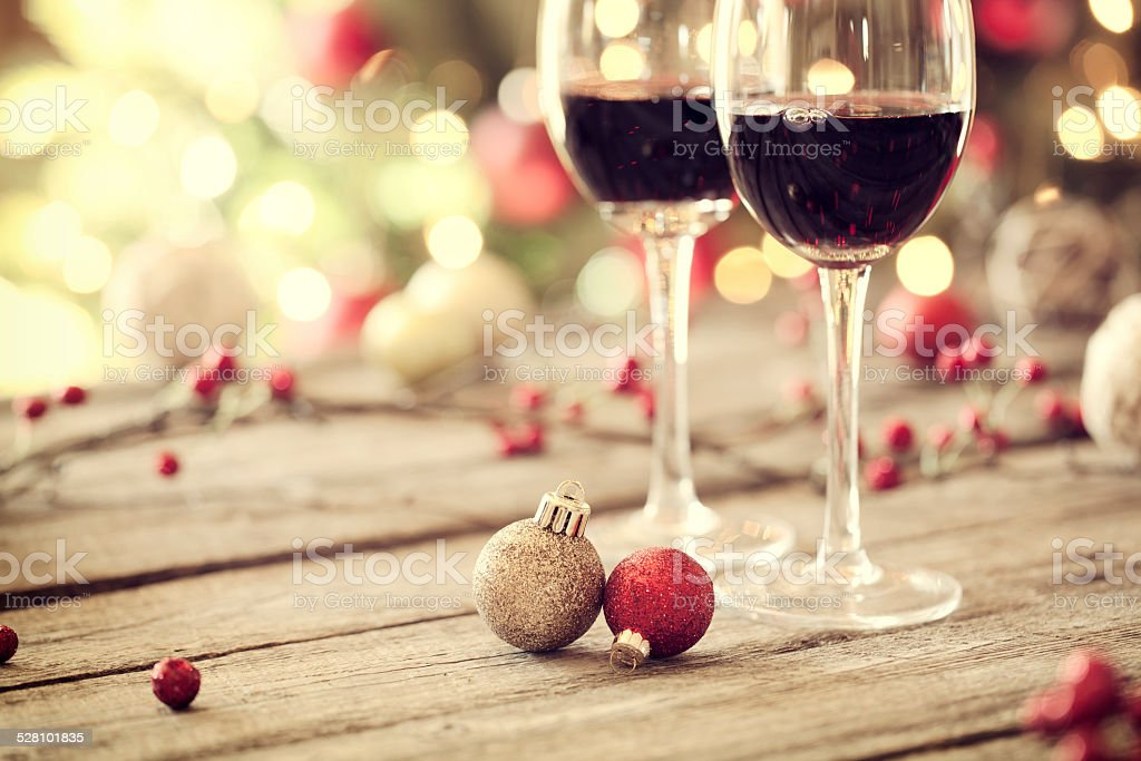 Christmas holiday red wine, old wood table, ornaments and tree