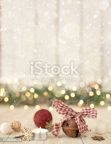 Christmas holiday rustic bell and natural fiber baubles on an old wood background with defocused lights and snowfall