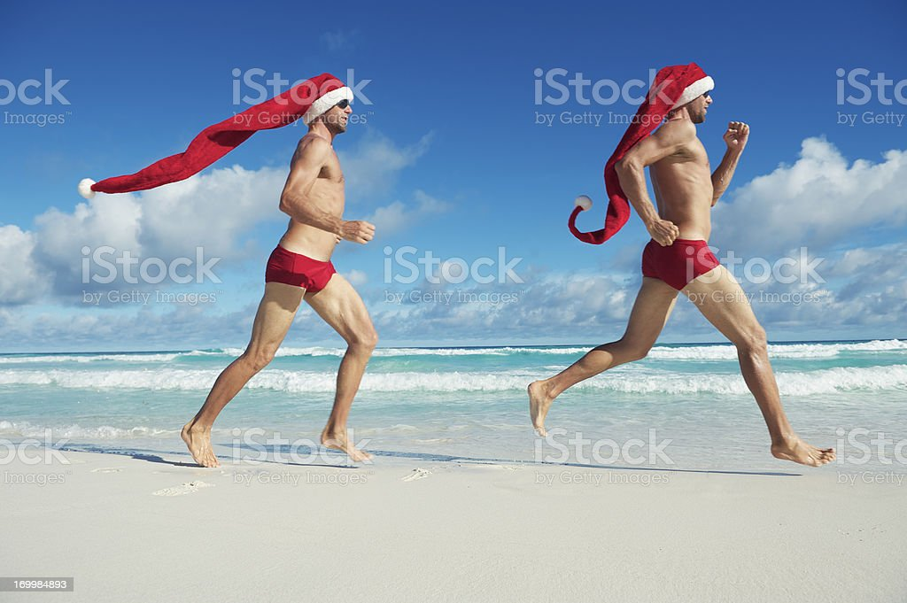 Christmas Holiday Santa Hat Twins Run Together on Tropical Beach stock photo