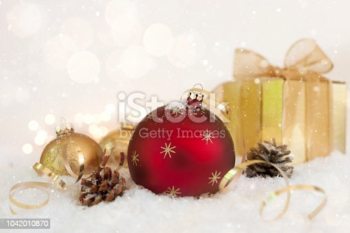 1020742072istockphoto Christmas Holiday Star Bauble and a Gift Against a Snowy Glowing White Background 1042010870