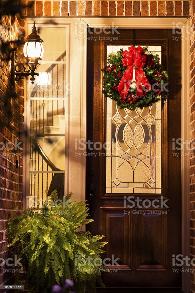 Christmas:  Holiday wreath on front door of home at night. stock photo