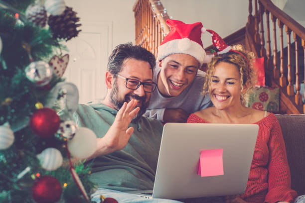 Christmas holidays winter family at home concept doing video calls to friends or parents using laptop comkputer and internet connection technology. - people enjoying video conference during christmas celebration stock photo
