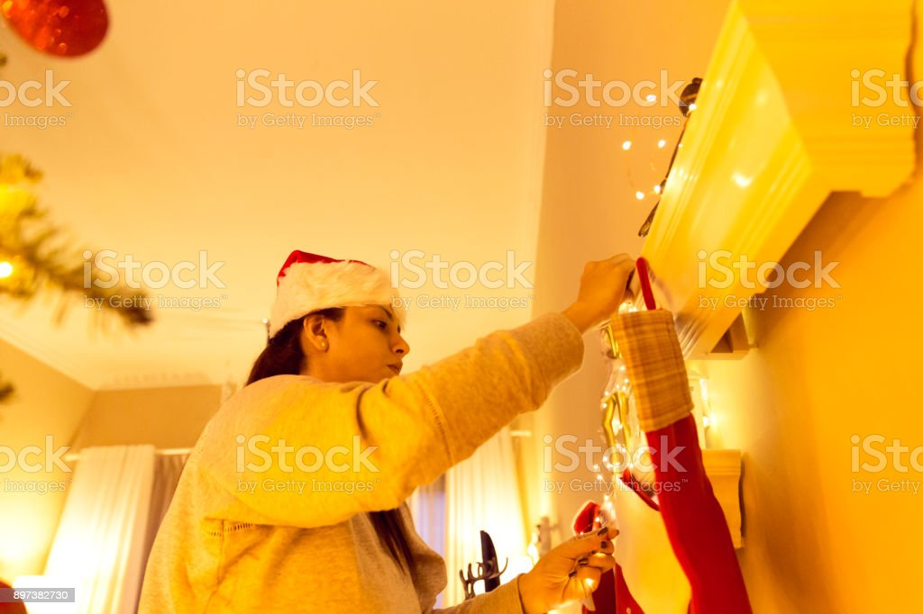 Low angle view of a woman wearing a Santa hat, while she is adding...