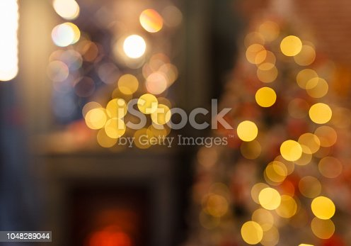 istock Christmas home room with tree and festive bokeh lighting, blurred holiday background 1048289044