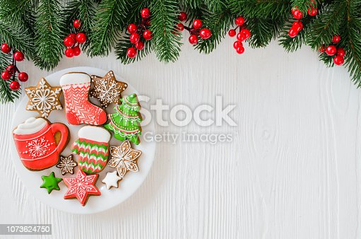 istock Christmas homemade gingerbread cookies and fir branches on white wooden background. 1073624750