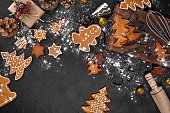 Christmas homemade gingerbread cookies, spices and cutting board on dark background with copy space for text top view. Holiday, celebration and cooking concept. New year and christmas postcard
