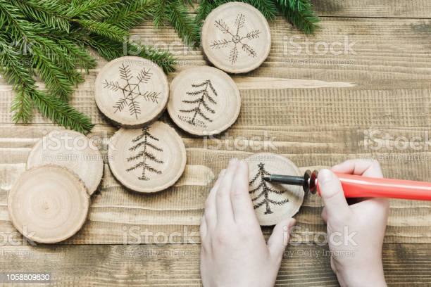 Photo of Christmas homemade pyrography toys. Wooden slice. Xmas decorations. Child makes gifts for relatives. View from above. Alternative decor.