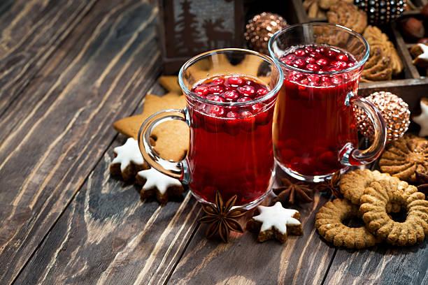 christmas hot cranberry tea and cookies on dark background - apfelweinkuchen stock-fotos und bilder