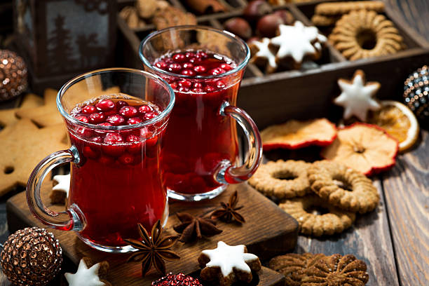 christmas hot cranberry tea and cookies on dark table - apfelweinkuchen stock-fotos und bilder
