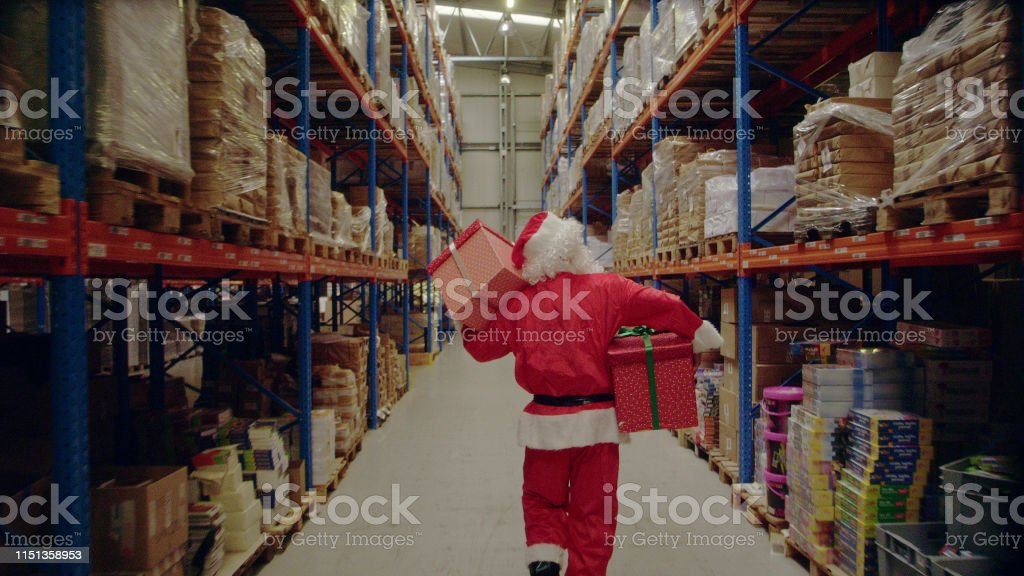 Christmas in a warehouse. Santa claus carrying christmas gifts - Royalty-free Adult Stock Photo