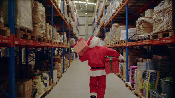 Christmas in a warehouse. Santa claus carrying christmas gifts stock photo