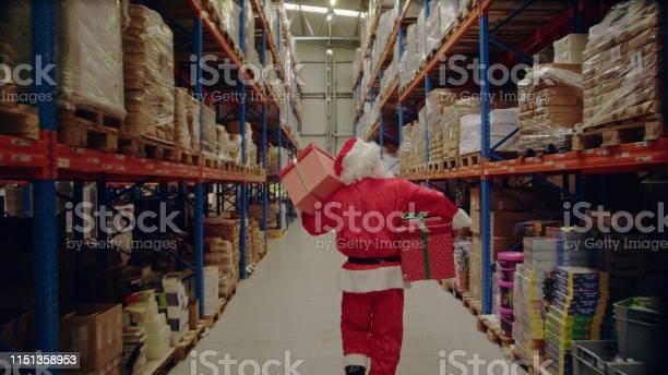 Christmas In A Warehouse Santa Claus Carrying Christmas Gifts Stock Photo - Download Image Now