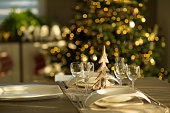 empty glasses and plates on dining table at home with blurred christmas tree and decoration in background