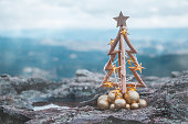 Rustic timber Christmas tree with gold star lights and baubles with Blue Mountains backdrop.  Seasonal holiday image, Christmas in July or Christmas in Blue Mountains, shallow dof, copy space.