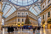 Milan, Italy - December 15, 2015: The Galleria Vittorio Emanuele II, named after the first king of the Kingdom of Italy, was built in the second half of the nineteenth century and is one of the world's oldest shopping malls. At Christmas this landmark of Milan welcomes visitors with a Christmas tree and lighted shop windows.