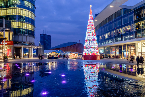 Milan, Italy - December 14, 2015: People strolling in Piazza Gae Aulenti, a raised circular urban square located in the Management Centre of Milan, built in 2012 and designed by Argentine architect Cesar Pelli. During the Christmas holiday it welcomes a modern Christmas tree and market stalls.