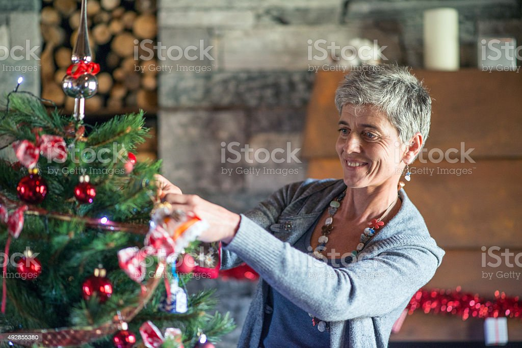 Christmas in mountain house: preparing the Christmas tree stock photo