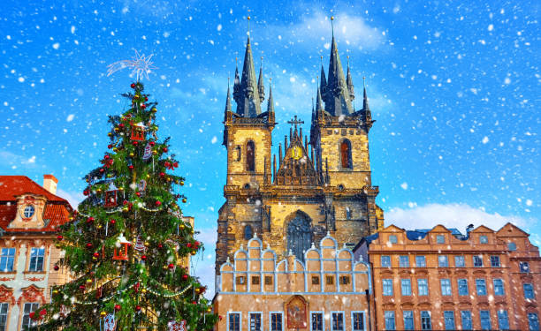 Christmas in Prague, Czech Republic Christmas in Prague, Czech Republic. Green christmas tree at central square old town (Staromestska) in front of Church of Our Lady Before Tyn. Snowfall, snow in sunny holiday winter day. tyn church stock pictures, royalty-free photos & images