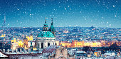 The Cathedral of Saint Nicholas in Prague on snowy Christmas evening.