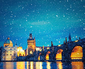 Charles Bridge in Prague on snowy Christmas evening.