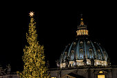 Vatican City, Vatican - December 18, 2018: Christmas Tree in Saint Peter Square with famous dome at night