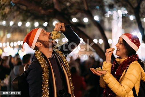 Happy couple celebrating New Year outside at night and eating grapes