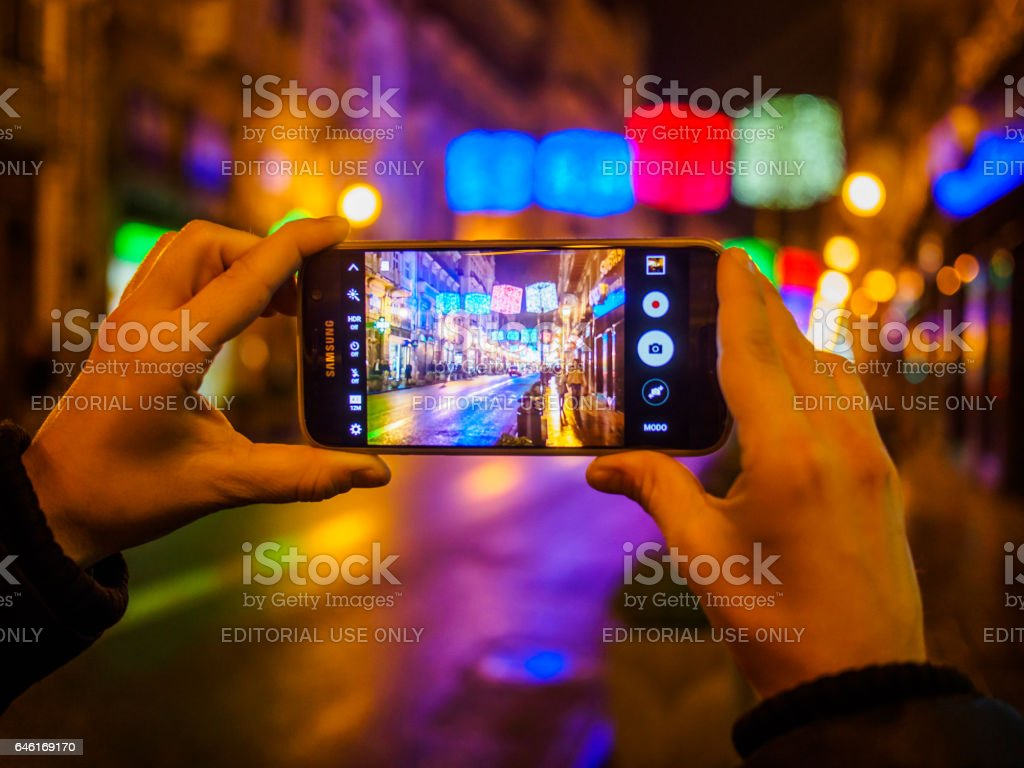 Christmas in Spain - Woman hands photographing Christmas lights stock photo
