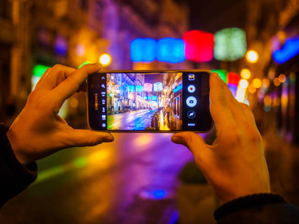 christmas in spain - woman hands photographing christmas lights - photo messaging stock photos and pictures