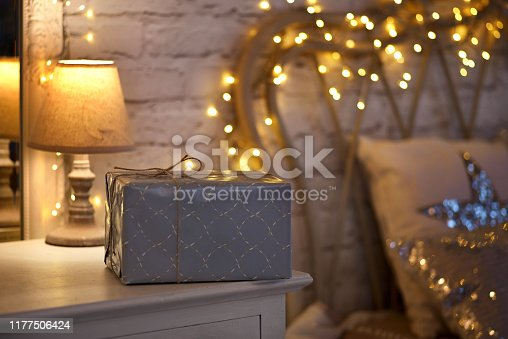 Christmas in the bedroom. Christmas interior on a white wall background with cozy lights. Gift box on the nightstand. Lots of pillows on the bed.