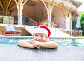 A photograph of a little boy with a santa's hat on in a swimming pool.