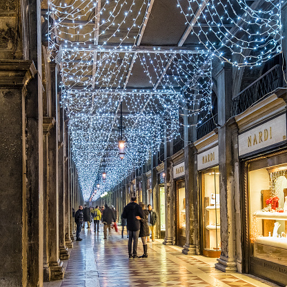 Venice, Italy - December 22, 2015: People strolling under the arcades around Piazza San Marco, St Mark's Square, decorated with Christmas lights. This is the main public square of Venice and one of the Italian landmarks.