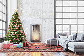 Interior showing a loft living room with a modern fireplace, large Christmas tree with decoration, lots of presents, carpet, armchair and garland. Coffee table with gray sofa. Carpet is decorative oriental with ornament. Large industrial windows.  Concrete panels on the wall. Copy space holiday template