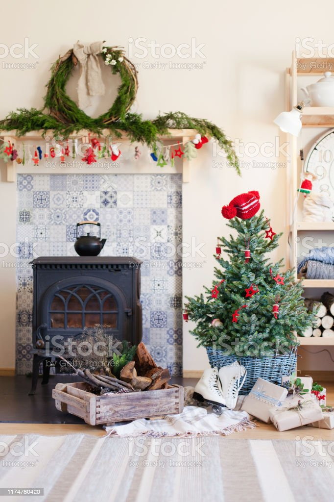 Christmas Interior With Decoration In Rustic Style Decorated Living Room In Cozy House Christmas Tree With Red Ornaments Gifts Presents Skates Are Under Fir Tree Near Wood Burning Stove Firewood Stock Photo