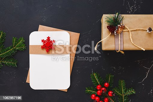 istock Christmas  invitation and greeting card decorated with  evergreen plants, red berry holly and gift 1062957196